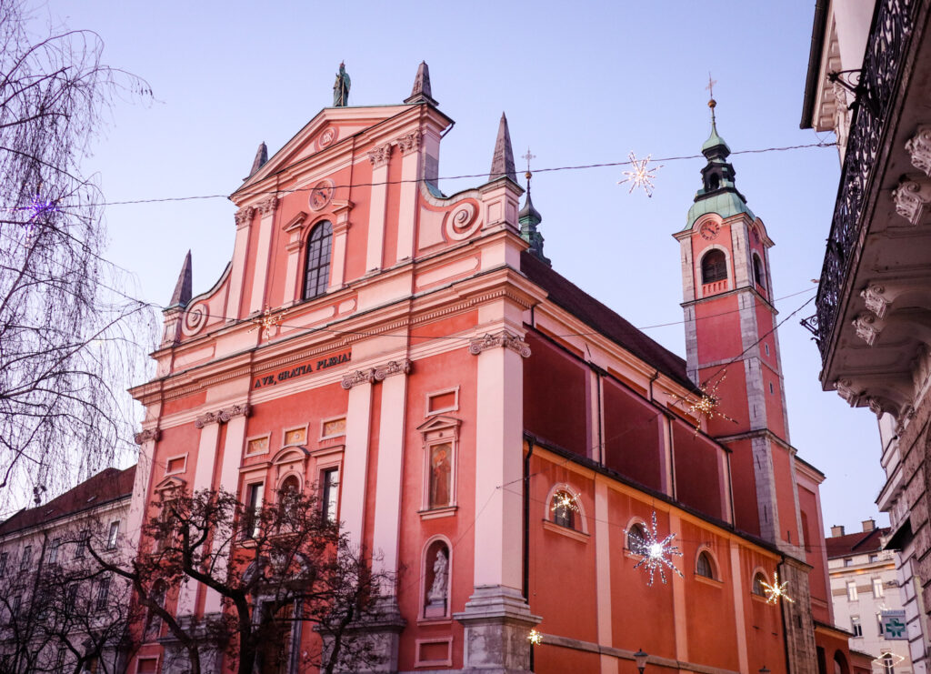 The pink facade of the Franciscan Church of the Annunciation in Ljubljana, Slovenia